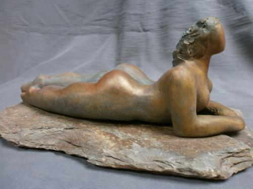femme cobra couchée sur socle pierre...Dimensions : 24 x 12 cm.